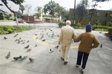 A elderly couple walks at the yard of the Canevaro old people's home in Lima